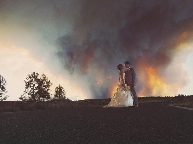 Michael Wolber e April Hartley foram evacuados do próprio casamento devido a um incêndio florestal, mas foram fotografados em uma cena incrível com as chamas ao fundo (Foto: Josh Newton/AP)
