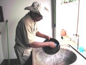O agente de saúde Áureo lava um bebedouro de animais