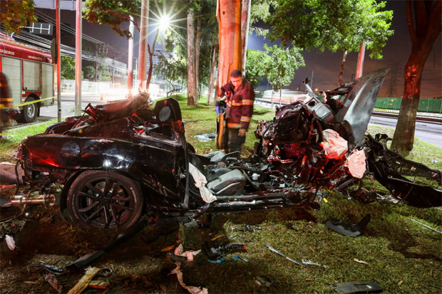 Bombeiro observa Camaro destruído após acidente que deixou duas pessoas feridas em São Paulo