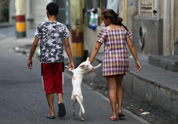 Cão passeia de mãos dadas com donos nas Filipinas (Foto: Aaron Favila/AP)