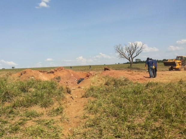Peritos usam escavadeira durante trabalhos no local do acidente em Guarda-Mor (Foto: Vanessa Pires/G1)