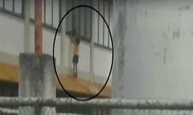 Mulher que passava perto da escola fotografou a criança do lado de fora da janela (foto: Reprodução Youtube)