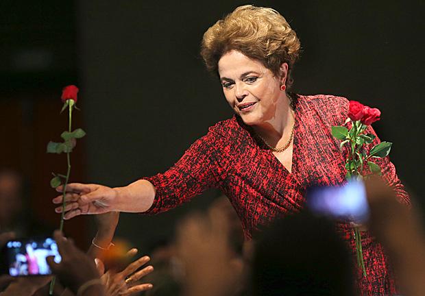 A presidente Dilma Rousseff recebe flores da plateia durante ato em Brasília