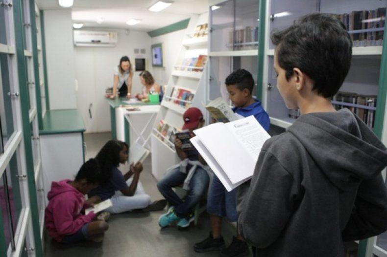 Alunos lendo dentro das instalações adaptadas do Ônibus Biblioteca (Foto: Asom)
