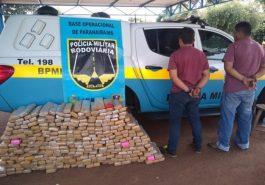 Dupla ao lado dos 300 tabletes de droga que estavam em fundos falsos da camionete. (Foto: Divulgação/PMR)