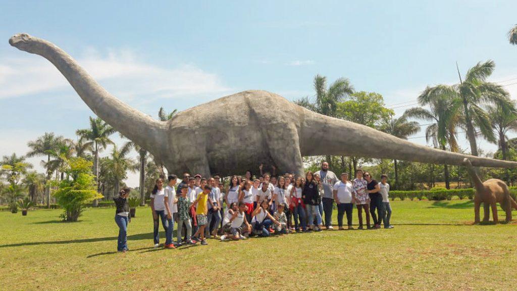 Alunos da Escola Juscelino ao lado da réplica de um titanossauro, um dos maiores animais que já viveram na região do Triângulo Mineiro (Foto: Escola Governador Juscelino)