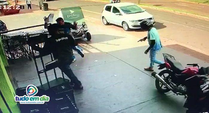 Bandido rende dois homens que estavam no parte externa de um dos supermercados (Foto: Reprodução do sistema de segurança)