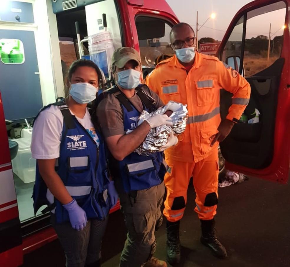 Equipe de resgate segurando o recém-nascido logo após ser encontrado no Anel Viário de Uberlândia — Foto: Corpo de Bombeiros/Divulgação